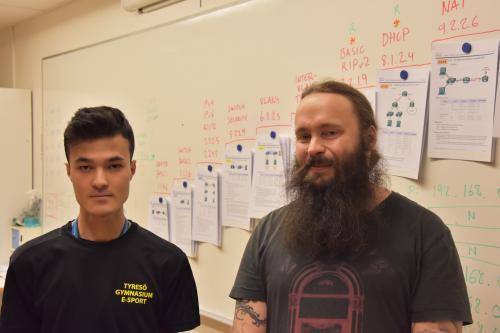 Datorteknikeleven Jacob tillsammans med läraren Pål framför ett CISCO-schema