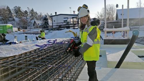 Anita Mattsson får hjälpa till att naja armeringen till bjälklaget i garaget under husen som byggs i Södergården.