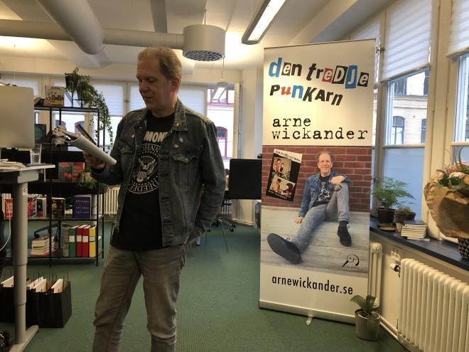 Arne Wickander läser högt om hur Lasse eller möjligen Hasse lagar sina skor med epoxy lim. I bakgrunden Arne Wickander.