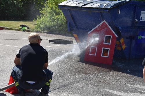 Brandman Johan Wissman hjälper barn att släcka elden.
