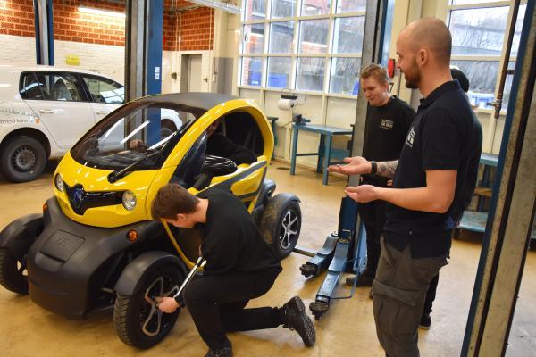 Fordonsläraren Oscar Eriksson lär elever vid fordonsprogrammet hur viktigt det är att efterdra hjulmuttrarna på den nya elbilen.