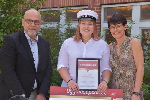 Bygmas representant Klas Widman, stipendiaten Madeleine Envall och rektor Lena Beskow poserar stolt utanför gymnasiet.