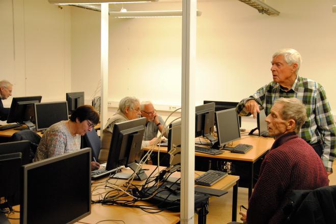 Seniorer som hjälper varandra med datorkunskap